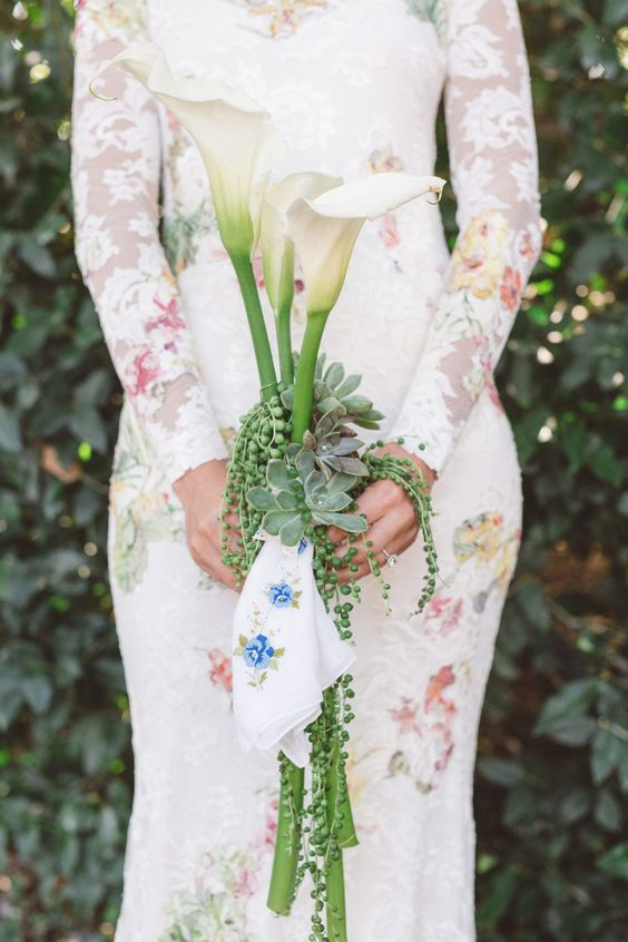 a very creative wedding bouquet of calla lilies, succulents and an embrodiered handkerchief is a very bright and cool idea