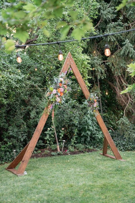a very simple rustic wedding arch of rich stained wood, bold blooms and greenery is a cool idea for a rustic or boho wedding