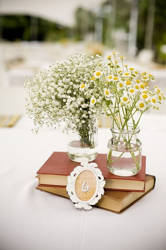 a vintage rustic wedding centerpiece of a stack of books and two vases, one with baby's breath and the second with daisies