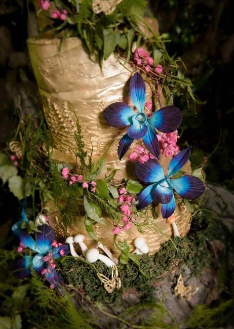 a whimsical enchanted forest wedding cake in gold, with fresh greenery, twigs, bright flowers and mini mushrooms looks very spectacular