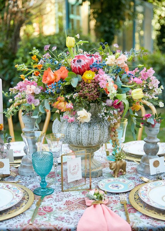 a whimsical secret garden wedding centerpiece in a vitnage bowl, with orange, yellow, pink and lilac blooms and berries plus greenery