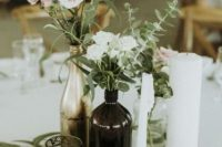 a whimsy cluster wedding centerpiece of blush and white garden roses and greenery, various candles and gilded candleholders