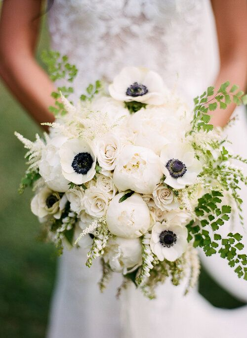 a white wedding bouquet of peonies, anemones, roses, greenery and blooming branches is a chic idea for a spring or summer wedding