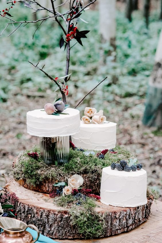 an assortment of enchanted forest wedding cakes - white buttercream ones topped with roses, fresh figs and blackberries for those who don't want a whimsy look