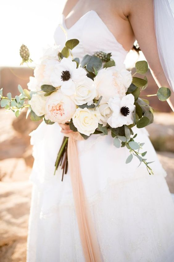 an elegant and chic spring or summer wedding bouquet of white roses, anemones and blush peonies with blush ribbons