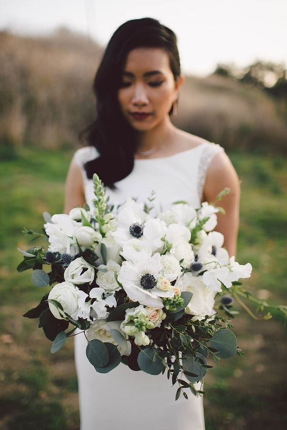 an elegant wedding bouquet of white anemones, roses, greenery and eucalyptus will fit a spring or summer wedding