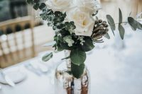 an elegant wedding centerpiece of white roses and eucalyptus in a mercury glass vase is a chic idea that you can compose yourself