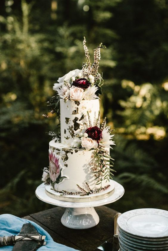 an enchanted forest wedding cake with gold leaf, white and burgundy blooms, greenery is a lovely idea for a forest wedding