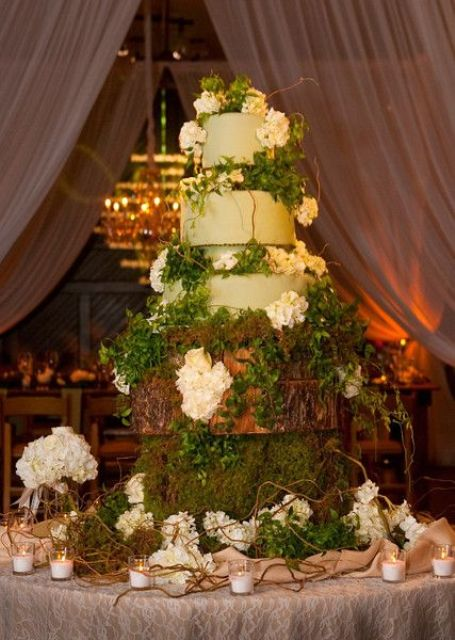 an enchanted forest wedding cake with light green tiers, with greenery, hydrangeas, twigs and moss presented on wooden slices