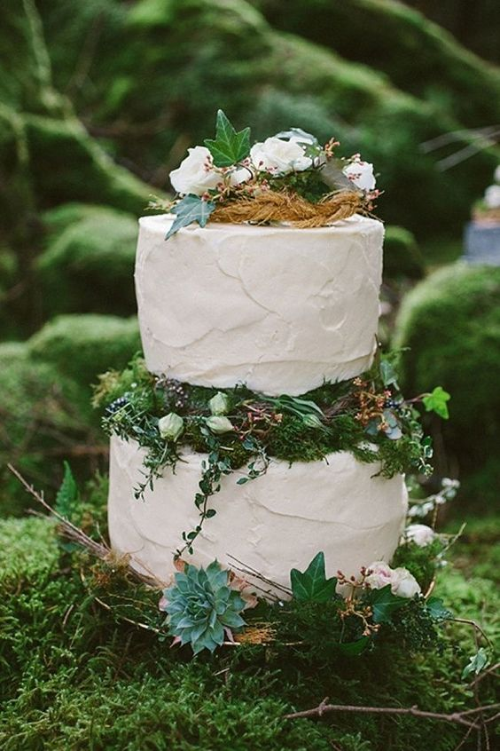 an enchanted forest wedding cake with textural white tiers, moss, greenery, white blooms and leaves plus succulents looks dreamy
