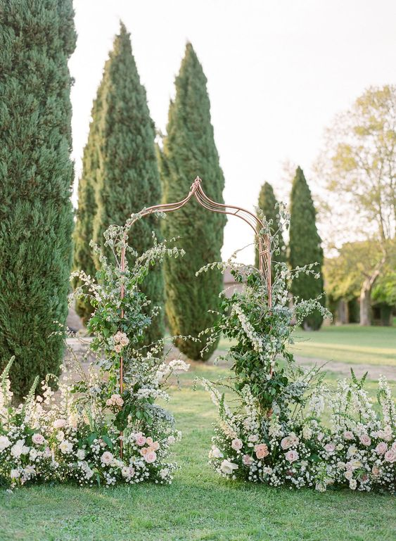 an enchanting secret garden wedding arch of a whimsy shape, with greenery and lots of blush blooms climbing up the arch