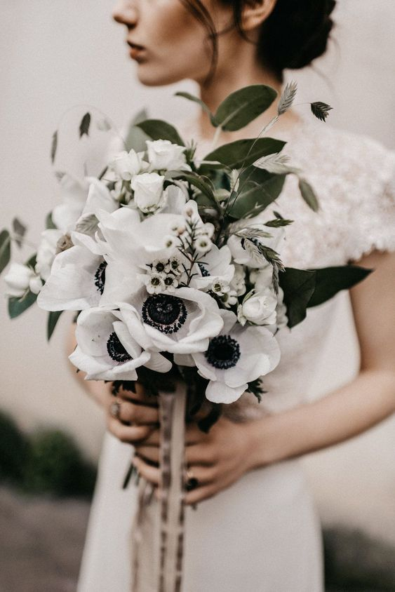 an eye-catchy wedding bouquet composed of waxflower and white anemones plus some grasses and foliage and ribbons to accessorize it