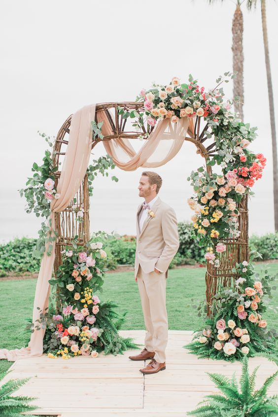 Groom stands at the altar during a colorful oceanfront Wedding at Ole Hanson in San Clemente, Ca with wedding photographer Lovisa Photo.
