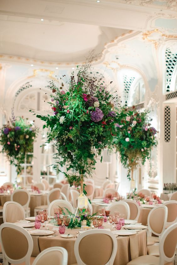 beautiful and bright tall wedding centerpieces of much greenery and bright flowers create a magical and charming ambience in the space