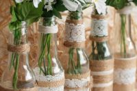 bottles wrapped with lace and twine, with baby's breath and daisies are simple DIY wedding centerpiece you can make fast