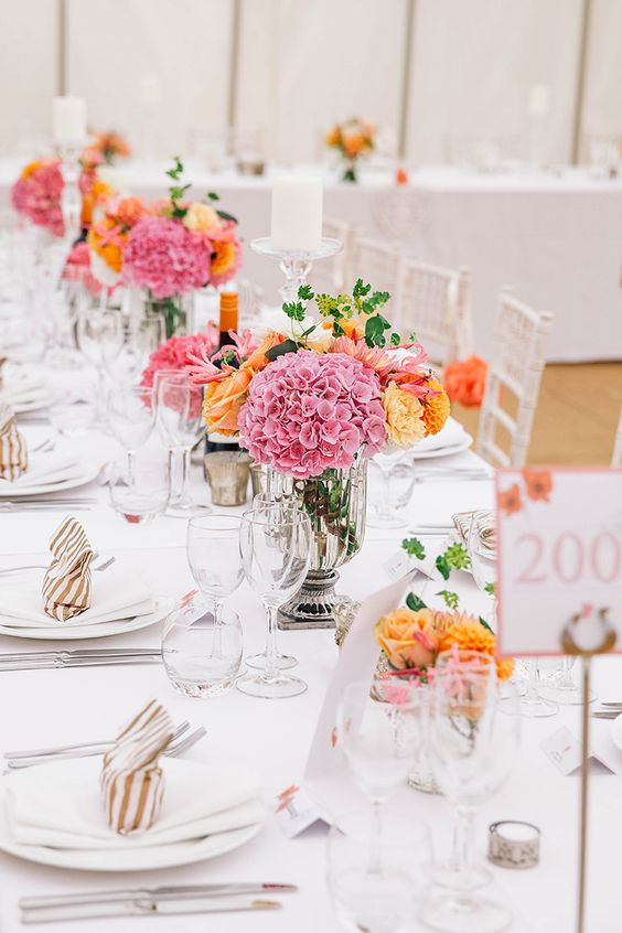 bright secret garden wedding centerpieces of pink and orange blooms and tall candles will make the space bolder and cooler