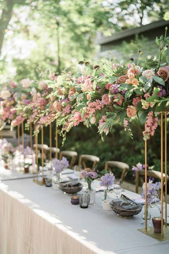 dreamy tall secret garden wedding centerpieces of blush and mauve blooms and greenery are a beautiful idea to rock