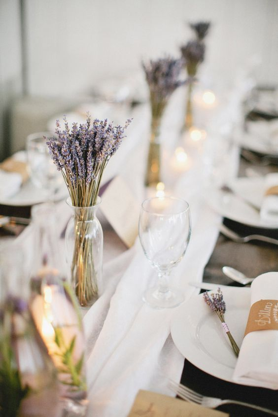 lovely lavender wedding centerpieces in sheer vases paired with candles and a white fabric runner look cute and lovely