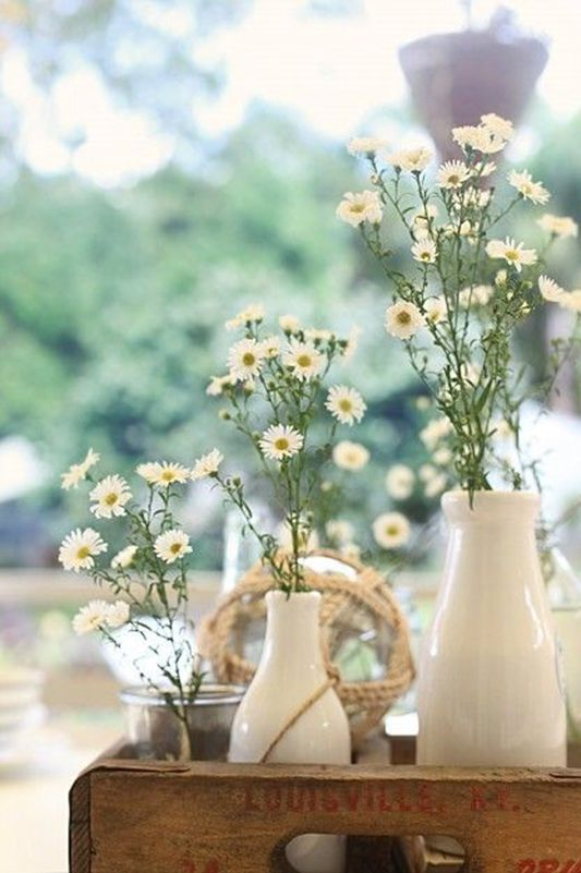 white vases with white daisies are lovely decorations for a relaxed rustic or boho summer wedding