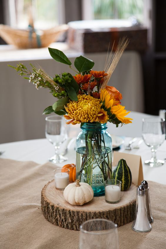 a blue mason jar filled with season flowers of football mums, sunflowers, hardy mums, wheat, open roses, and foliage plus gourds