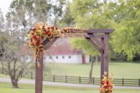 02 a fall backyard wedding ceremony space with a stained arch, bold blooms and greenery, pumpkins and potted blooms around it