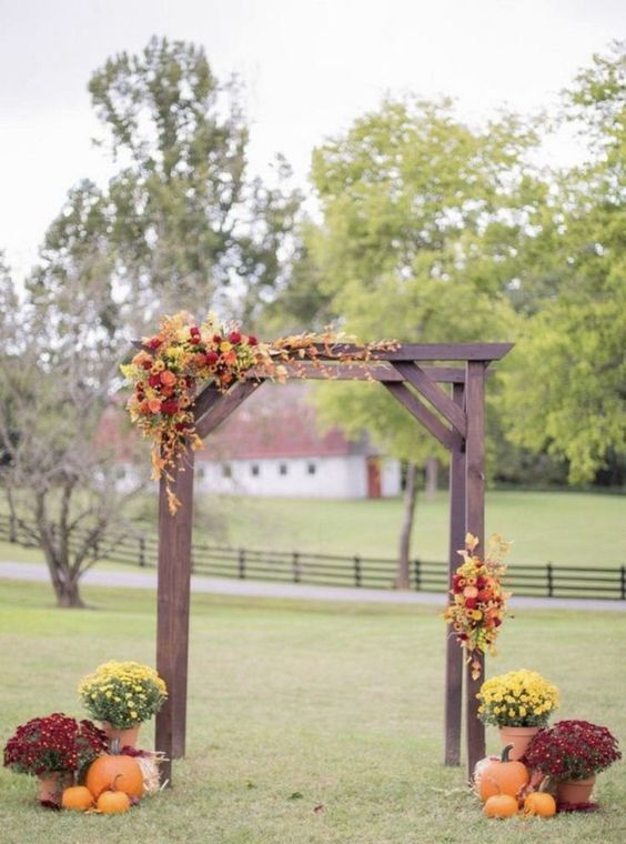 a fall backyard wedding ceremony space with a stained arch, bold blooms and greenery, pumpkins and potted blooms around it