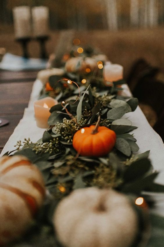 a beautiful fall rustic wedding table runner of eucalyptus, pumpkins, LED lights and candles is a lovely solution