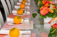 03 a colorful modern bridal shower table with pink placemats, citrus as card holders, bold blooms and greenery and simple glasses
