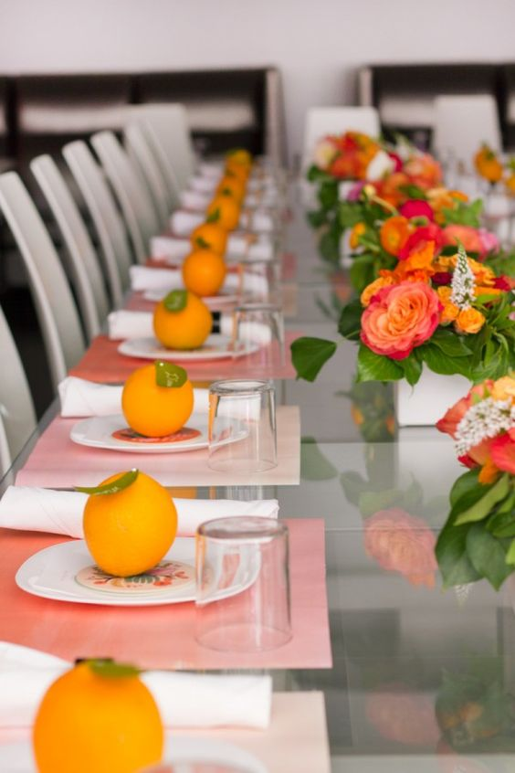 a colorful modern bridal shower table with pink placemats, citrus as card holders, bold blooms and greenery and simple glasses