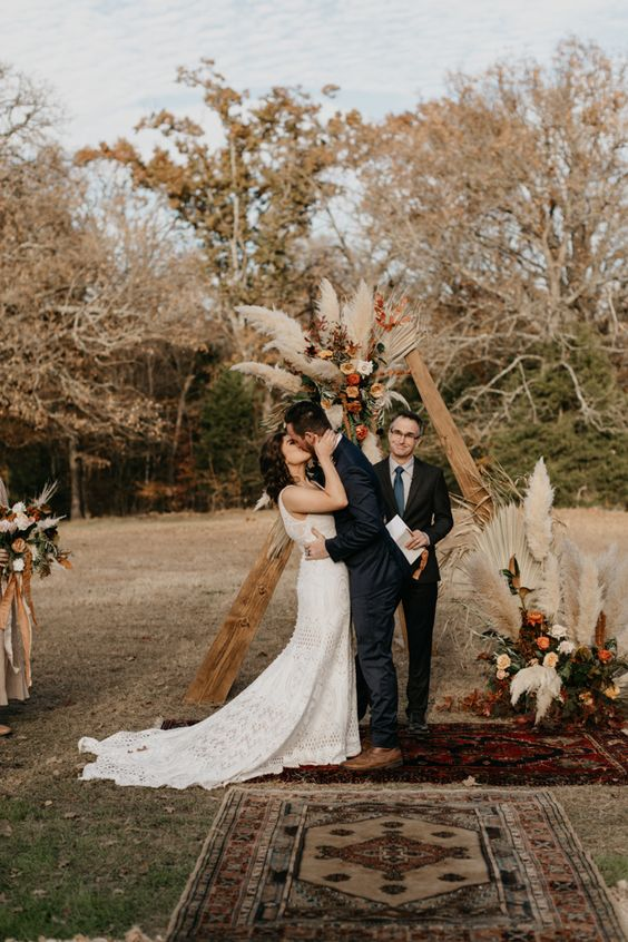 a boho fall backyard wedding ceremony space with a triangle arh decorated with pastel blooms and pampas grass and boho rugs