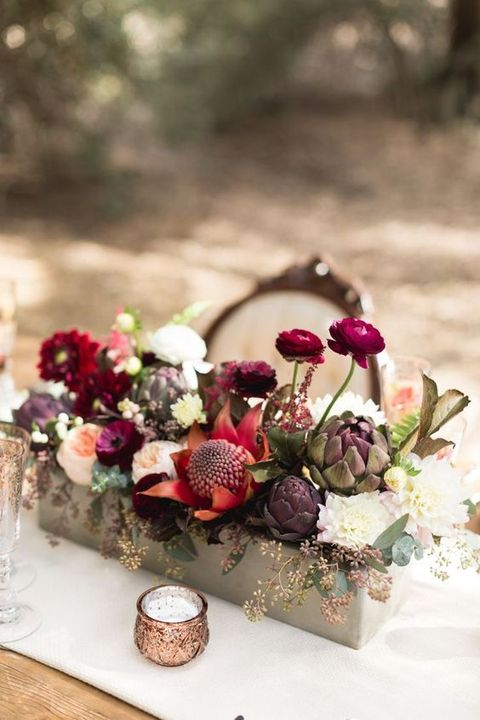 a bold rustic fall wedding centerpiece of red, fuchsia, deep purple, blush blooms, artichokes and some eucalyptus is a sumptuous idea