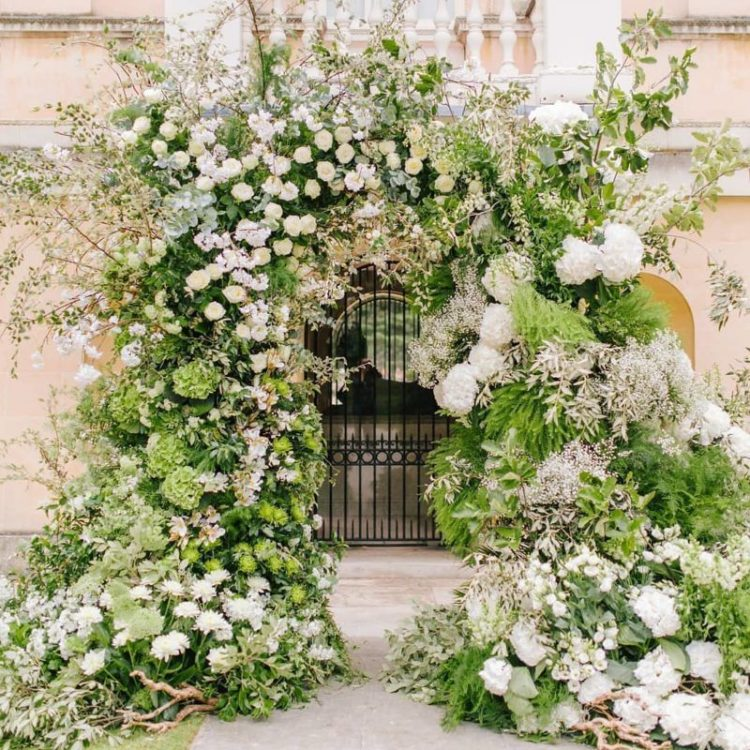 a breathtaking overgrown floral wedding arch with lots of textural greenery, twigs and branches and pastel blooms