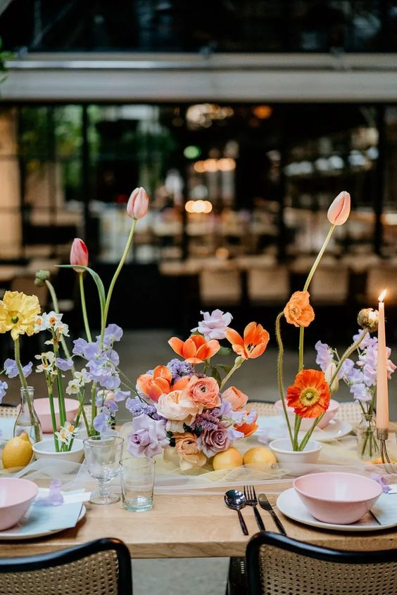 a cool colorful modern bridal shower tablescape with lilac, yellow, red, orange blooms, blush candles, pastel porcelain and glasses