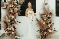 05 a boho backyard wedding ceremony space with a cool pampas grass, blush roses and dark foliage altar that wows