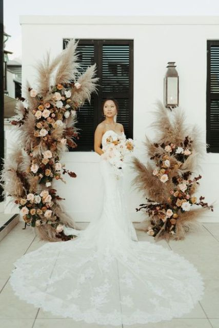 a boho backyard wedding ceremony space with a cool pampas grass, blush roses and dark foliage altar that wows