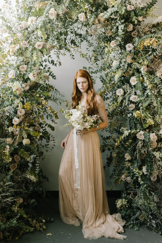 a breathtaking overgrown flower wedding arch with blush blooms and tons of eucalyptus covering it is amazing