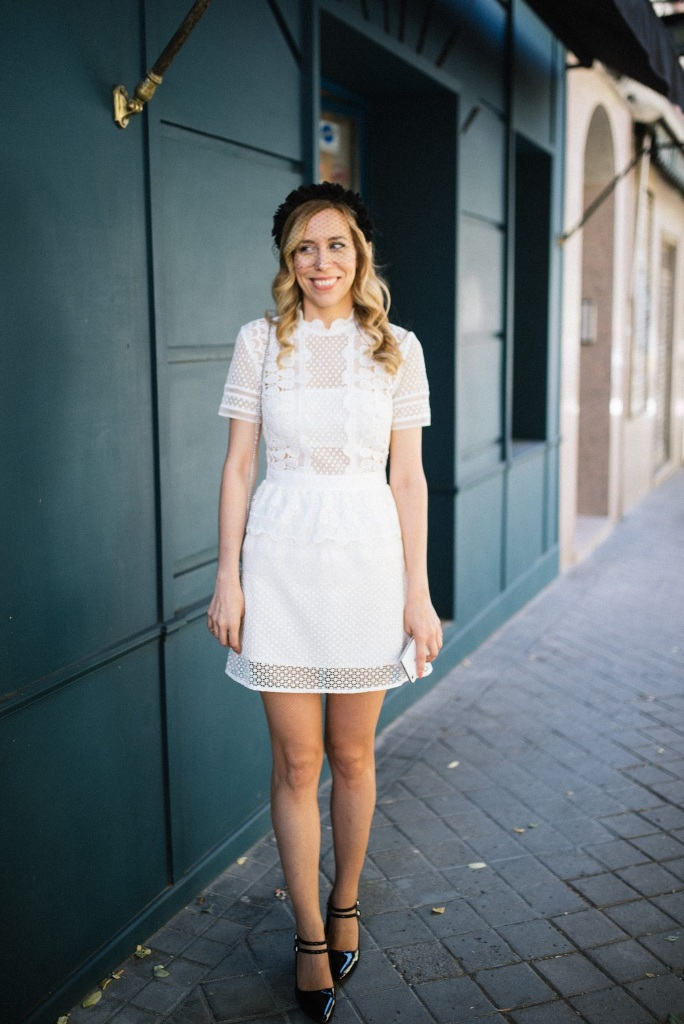 a cute mini wedding dress with a polka dot overdress, strategically placed plain parts, short sleeves, a ruffle neckline, black heels and a birdcage veil