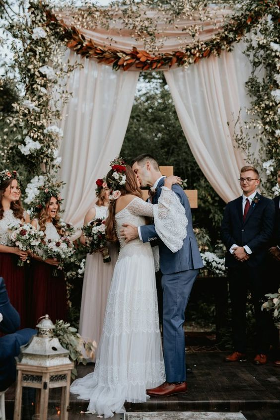 a boho backyard fall wedding space with a curtain and magnolia leaf backdrop, white blooms and greenery, candle lanters is amazing