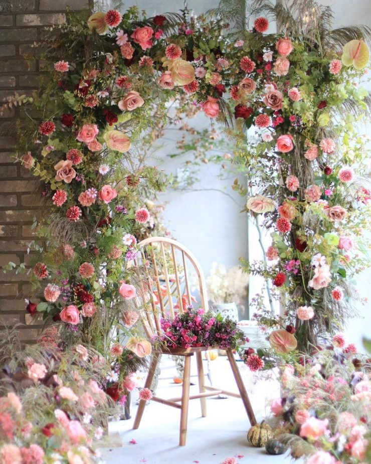 a bright overgrown flower wedding arch with lots of greenery, pink, burgundy and deep red blooms will wow you and your guests