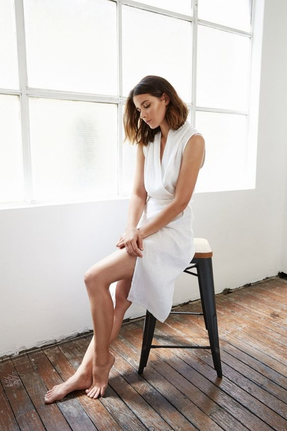 a casual white knee dress with a V-neckline, no sleeves and a front slit is a simple and stylish idea to try