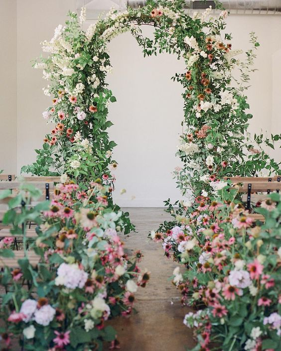 a gorgeous wedding ceremony space with lots of pink and blush overgrown wedding blooms and a matching lush wedding arch with greenery