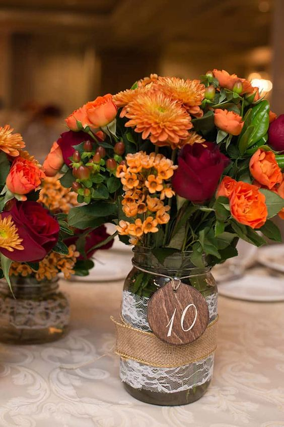 a jar with burlap and lace, a plywood tag, bold orange and burgundy blooms, greenery and berries is a lovely idea of a rustic fall centerpiece
