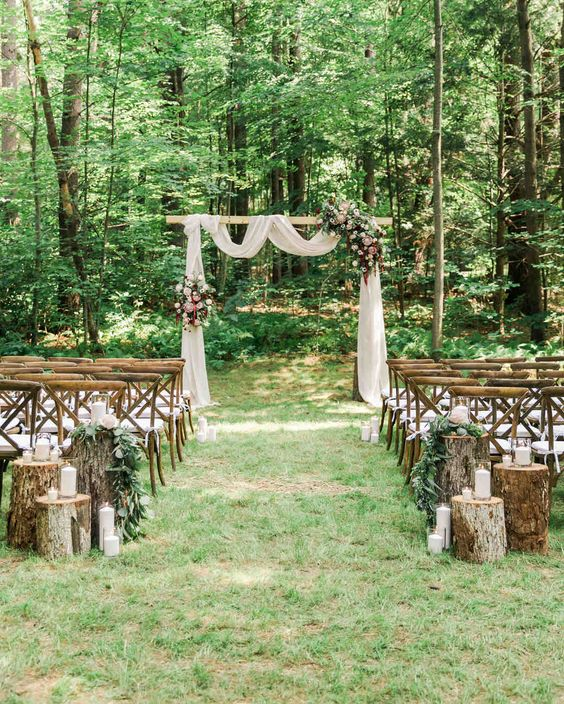 a lovely fall backyard wedding ceremony space with an arch with white fabruc, pink and bold blooms and greenery and some tree stump decor