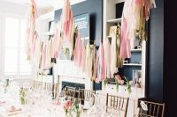 08 a modern and pastel bridal shower tablescape with pink napkins, pink ranunculus, gold cutlery, elegant glasses and pink tassels over the table