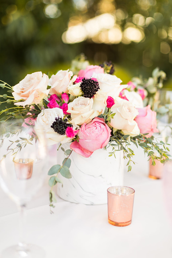 a modern and cool bridal shower centerpiece in a marble vase, with pink and white roses, black blooms and greenery is wow