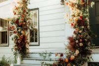 09 a porch styled as a wedding ceremony space with neutral, rust, burgundy blooms, greenery and candles is a lovely idea for a fall wedding