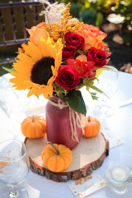 a simple and colorful wedding centerpiece of a red jar with sunflowers, red roses, dried grasses and pumpkins ona  wood slice