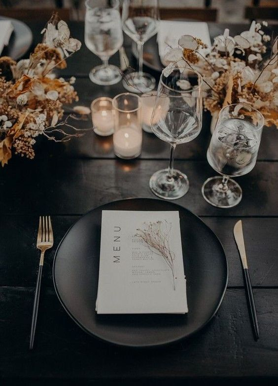 a chic modern fall wedding tablescape with an uncovered table, dried blooms and twigs, black plates and cutlery, candles