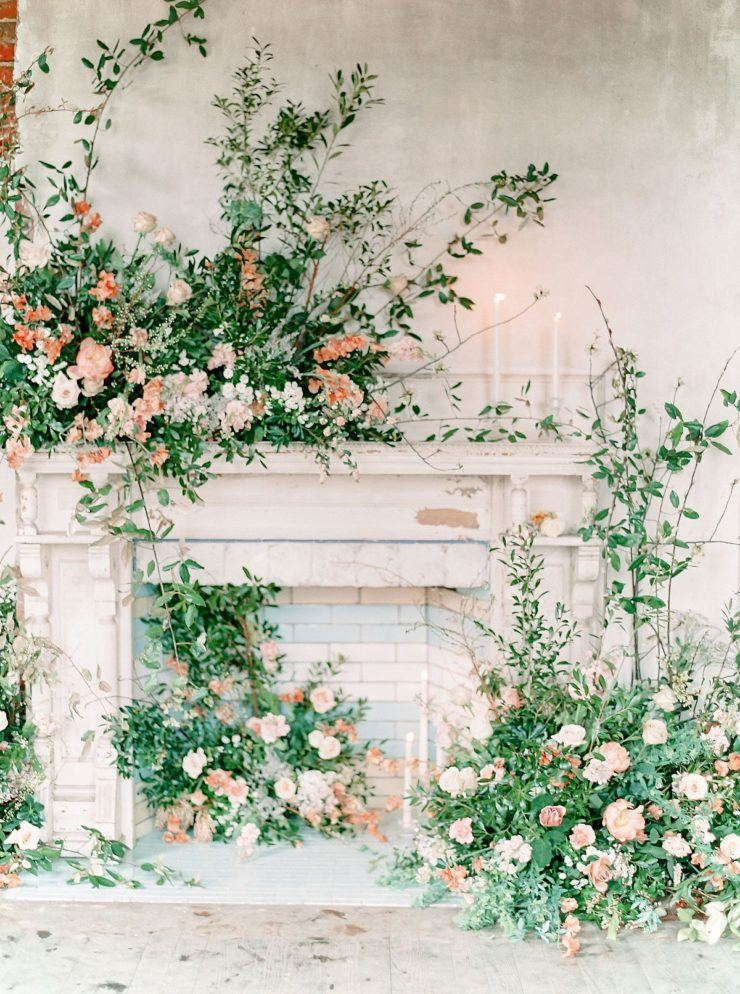 a fireplace space with lots of overgrown pink and peach blooms and greenery is a gorgeous wedding ceremony space