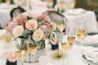 10 a modern and chic bridal shower tablescape with pink and blush blooms, pale leaves, gilded glasses, black plates and black cutlery